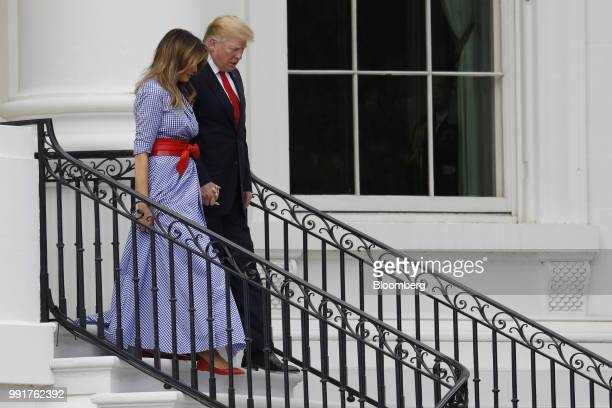 US President Donald Trump right and First Lady Melania Trump walk down a flight of stairs as they arrive at a picnic for military families in...