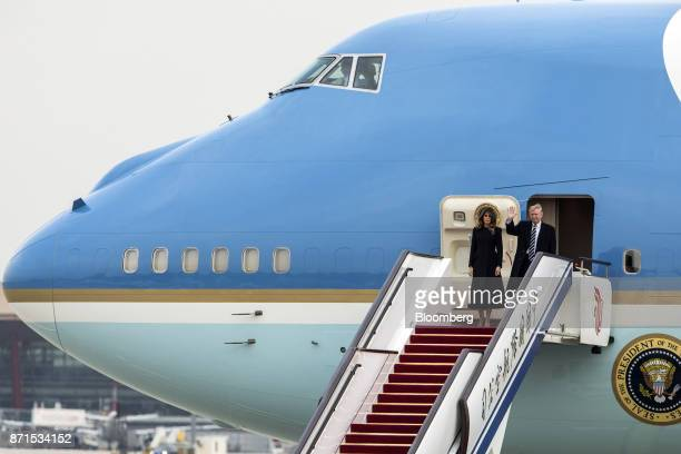US President Donald Trump right and US First Lady Melania Trump disembark from Air Force One at the Beijing Capitol Airport in Beijing China on...