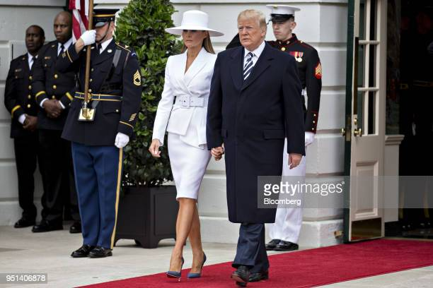 S President Donald Trump right and US First Lady Melania Trump walk out of the White House to greet Emmanuel Macron France's president and Brigitte...