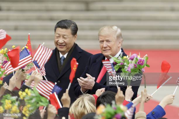 S President Donald Trump right and Xi Jinping China's president greet attendees waving American and Chinese national flags during a welcome ceremony...