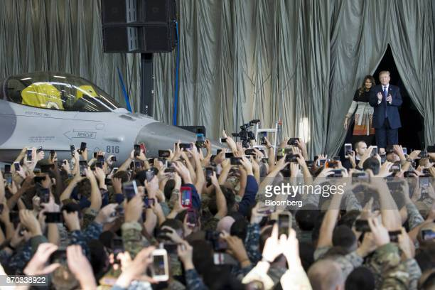 US President Donald Trump right applauds as he arrives at a hanger with US First Lady Melania Trump second right to address US military personnel at...