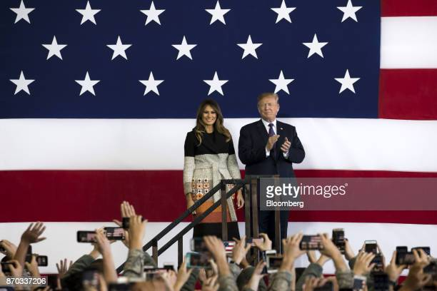 US President Donald Trump right applauds as US First Lady Melania Trump looks on before addressing US military personnel at Yokota Air Base in Fussa...