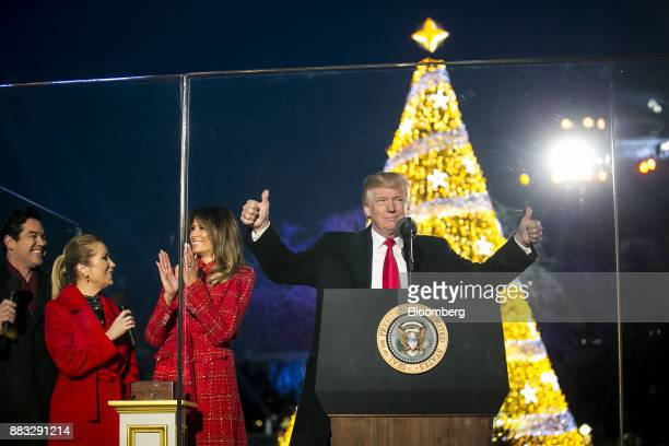 US President Donald Trump right gestures as US First Lady Melania Trump applauds during the 95th Annual National Christmas Tree Lighting in...