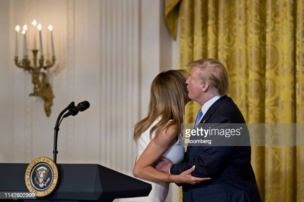 US President Donald Trump right gives a kiss to First Lady Melania Trump during a Celebration of Military Mothers event in the East Room of the White...