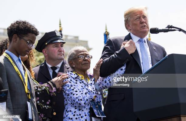 President Donald Trump right holds the hand of Adrianna Valoy while speaking about her daughter New York Police Department Detective Miosotis Familia...