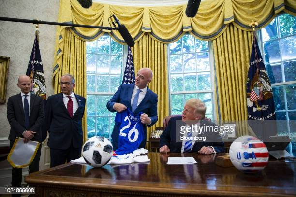 US President Donald Trump right is interrupted by a reporter as Gianni Infantino president of FIFA second right presents him with a game jersey...