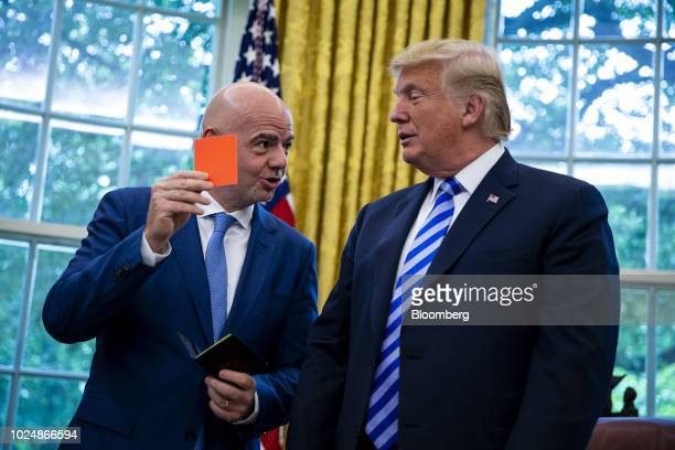 US President Donald Trump right is presented a referee red card by Gianni Infantino president of FIFA in the Oval Office of the White House in...