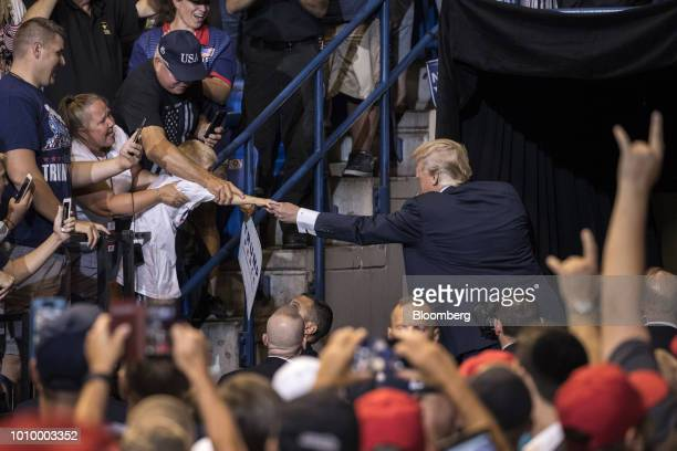 US President Donald Trump right reaches out to shake hands with a boy at a rally in WilkesBarre Pennsylvania US on Thursday Aug 2 2018 Trump tweeted...