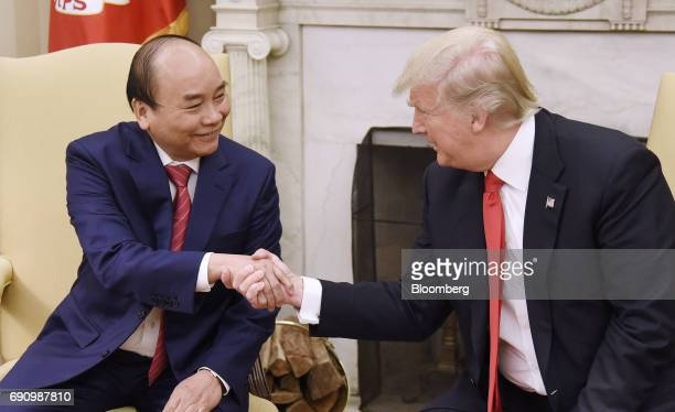 US President Donald Trump right shakes hands with Nguyen Xuan Phuc Vietnam's prime minister during a meeting in the Oval Office of the White House in...