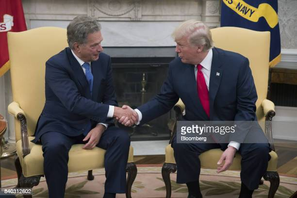 US President Donald Trump right shakes hands with Sauli Niinisto Finland's president during a meeting in the Oval Office of the White House in...