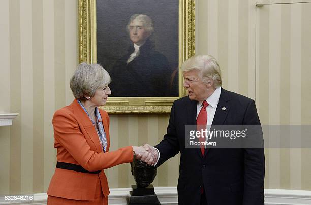 US President Donald Trump right shakes hands with Theresa May UK prime minister in the Oval Office of the White House in Washington DC US on Friday...