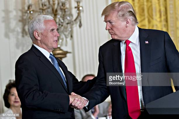 US President Donald Trump right shakes hands with US Vice President Mike Pence during a National Space Council meeting in the East Room of the White...