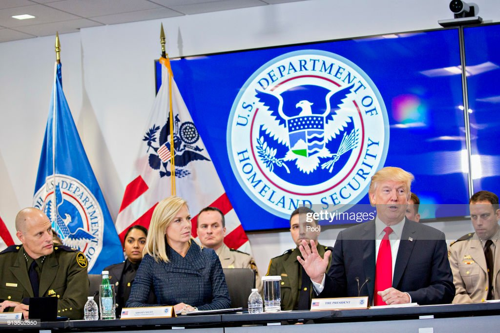 U.S. President Donald Trump, right, speaks as Kirstjen Nielsen, secretary of Homeland Security, left, listens while participating in a Customs and Border Protection (CBP) roundtable discussion after touring the CBP National Targeting Center February 2, 2018 in Sterling, Virginia. Trump is looking to ratchet up pressure on lawmakers to consider the immigration proposal he unveiled in Tuesday's State of the Union using the visit as an opportunity to again argue his proposal would bolster the country's borders.