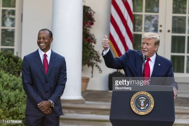 US President Donald Trump right speaks as Tiger Woods professional golfer and cofounder of the Tiger Woods Foundation smiles during a Presidential...