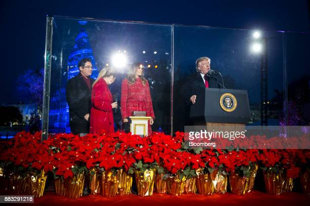 US President Donald Trump right speaks as US First Lady Melania Trump second right listens during the 95th Annual National Christmas Tree Lighting in...