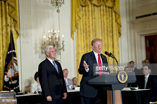 US President Donald Trump right speaks as US Vice President Mike Pence listens during a National Space Council meeting in the East Room of the White...