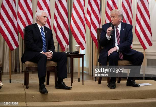 US President Donald Trump right speaks while Vice President Mike Pence listens during an event on opening schools in the State Dining Room of the...