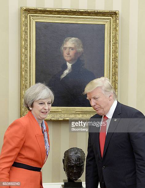 US President Donald Trump right stands for a photograph with Theresa May UK prime minister in the Oval Office of the White House in Washington DC US...