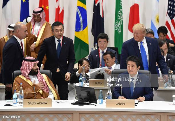 President Donald Trump, right, walks past Mohammed Bin Salman, Saudi Arabia's crown prince, front row left, and Shinzo Abe, Japan's prime minister,...