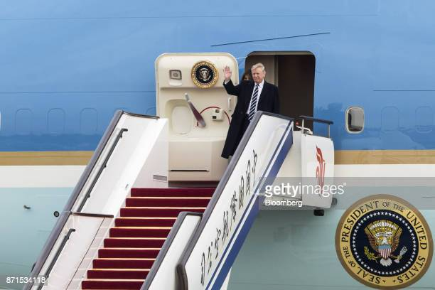 US President Donald Trump right waves as he and US First lady Melania Trump disembark from Air Force One at the Beijing Capitol Airport in Beijing...