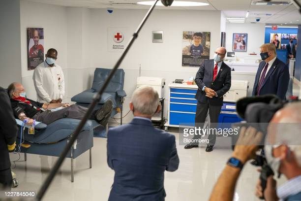 President Donald Trump, right, wears a protective mask as patient donates plasma at the American Red Cross National Headquarters in Washington, D.C.,...
