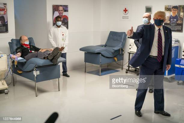 President Donald Trump, right, wears a protective mask while giving a thumbs up as patient donates plasma, left, at the American Red Cross National...
