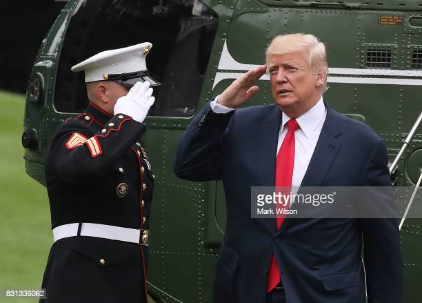 President Donald Trump salutes a US Marine after landing on the South Lawn at the White House on August 14 2017 in Washington DC Later today...