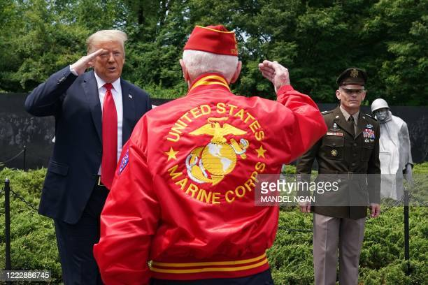 US President Donald Trump salutes a veteran during a visit to the Korean War Veterans Memorial in Washington DC on June 25 2020 North and South Korea...