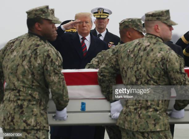 S President Donald Trump salutes as a military carry team moves the transfer case containing the remains of Scott A Wirtz during a dignified transfer...