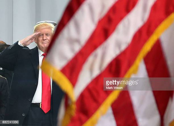 S President Donald Trump salutes as an American flag passes the inaugural parade reviewing stand in front of the White House on January 20 2017 in...