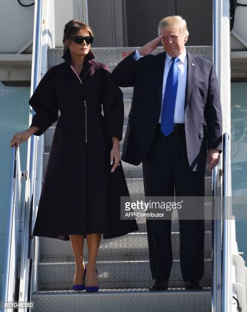 US President Donald Trump salutes as First Lady Melania looks on prior to departing from US Yokota Air Base in Tokyo on November 7 2017 Trump's...