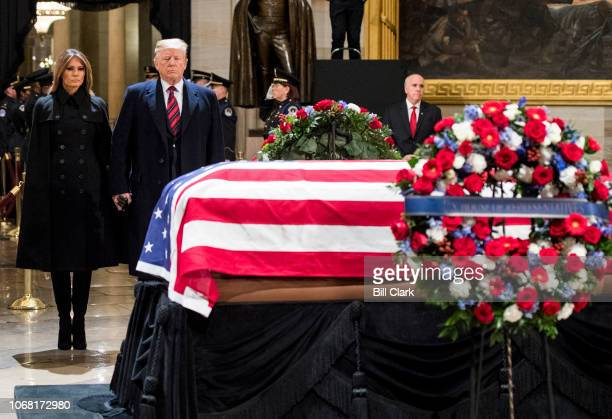 President Donald Trump salutes as First Lady Melania Trump pay their respect at former President George HW Bush's casket in the Capitol Rotunda on...