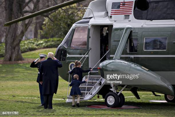 US President Donald Trump salutes as he boards Marine One on the South Lawn of the White House with his grandchildren Arabella Kushner right and...