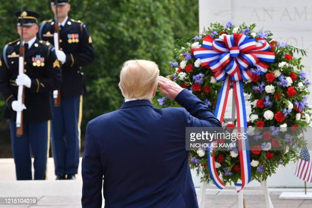 US President Donald Trump salutes as he participates in a Wreath Laying Ceremony at the Tomb of the Unknown Soldier at Arlington National Cemetery to...