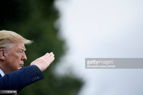 President Donald Trump salutes during a welcome ceremony for Chairman of the Joint Chiefs of Staff Army General Mark Milley at Fort Myer September 30...