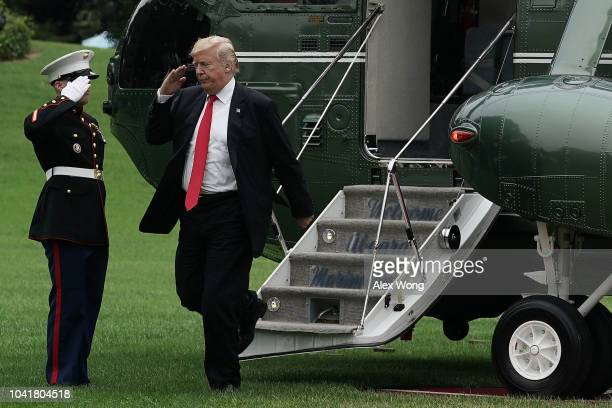 S President Donald Trump salutes to a Marine as he steps off the Marine One after he landed at the South Lawn of the White House September 27 2018 in...