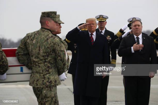 S President Donald Trump salutes while joined by Secretary of State Mike Pompeo as a military carry team moves the transfer case containing the...
