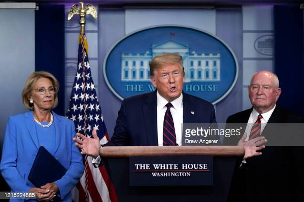 S President Donald Trump sas Secretary of Education Betsy DeVos and Secretary of Agriculture Sonny Perdue look on during a briefing on the...