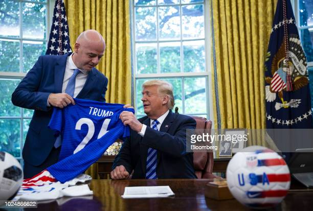 US President Donald Trump seated is presented a game jersey by Gianni Infantino president of FIFA in the Oval Office of the White House in Washington...