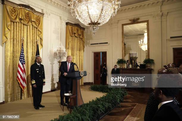 US President Donald Trump second left speaks as Vice Admiral Jerome Adams the US Surgeon General left listens during a National African American...
