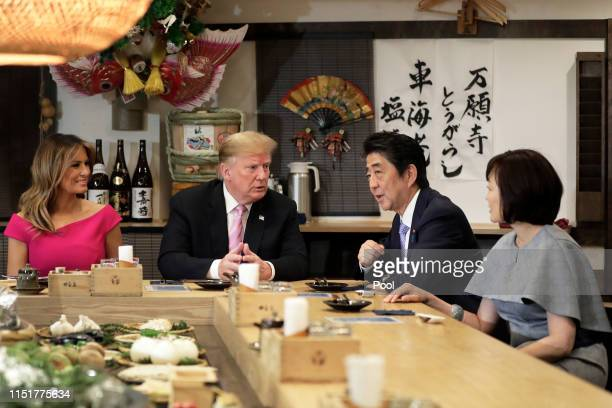 S President Donald Trump second left speaks with Shinzo Abe Japan's Prime Minister second right while sitting at a counter with First Lady Melania...