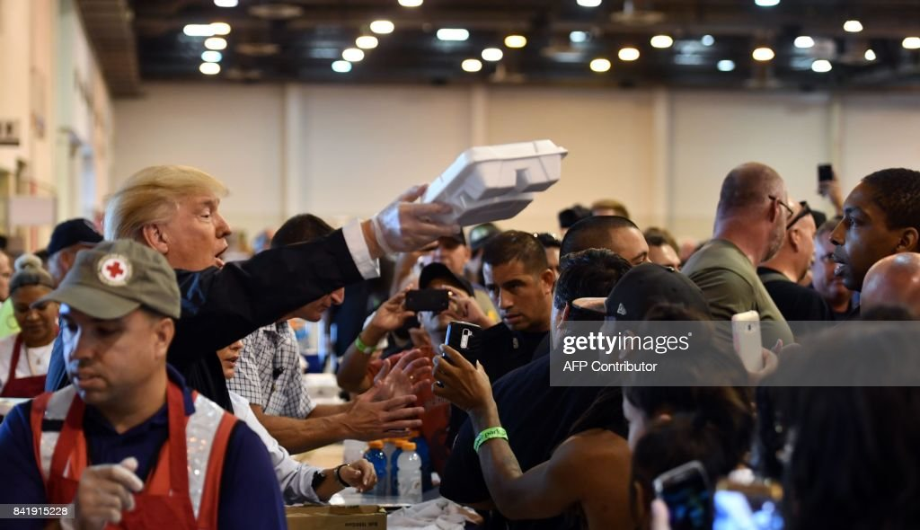 President Donald Trump serves food to Hurricane Harvey victims at NRG Center in Houston on September 2, 2017. / AFP PHOTO / Nicholas Kamm