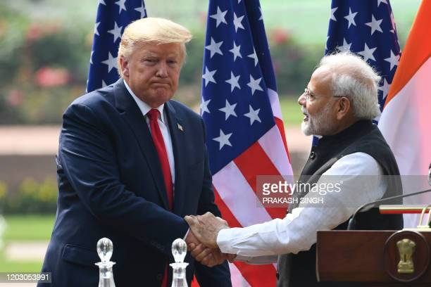 US President Donald Trump shaeks hands with India's Prime Minister Narendra Modi listens during a joint press conference at Hyderabad House in New...