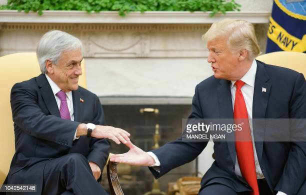 US President Donald Trump shake hands during a meeting with Chile's President Sebastian Pinera in the Oval Office of the White House in Washington DC...