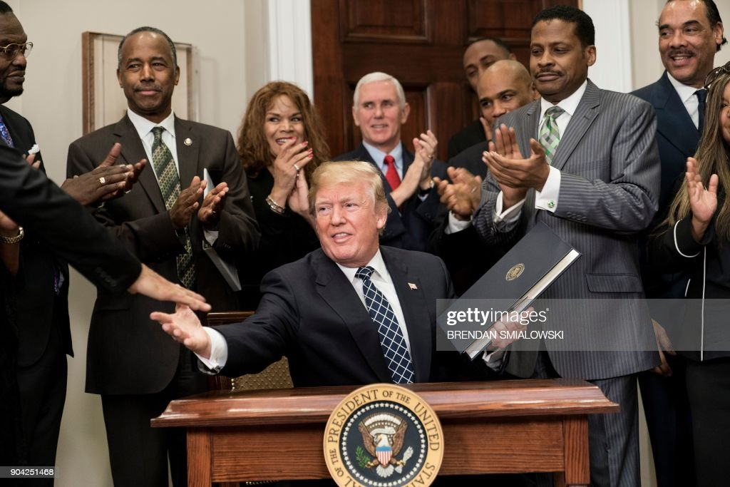 President Donald Trump shakes hands after signing a proclamation during an event about Martin Luther King Jr. in the Roosevelt Room of the White House January 12, 2018 in Washington, DC. / AFP PHOTO / Brendan Smialowski