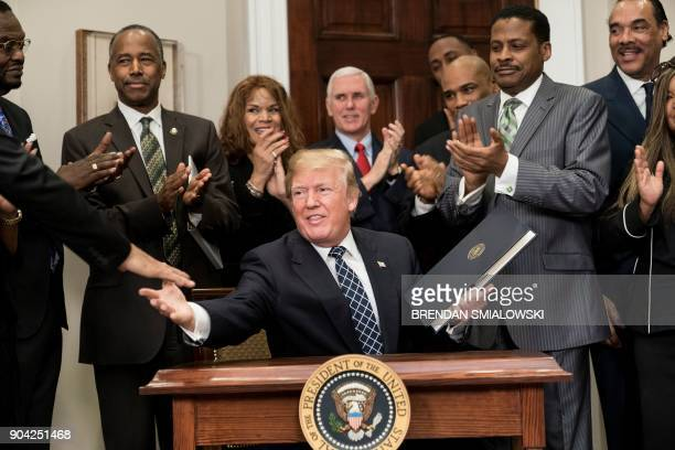 President Donald Trump shakes hands after signing a proclamation during an event about Martin Luther King Jr in the Roosevelt Room of the White House...