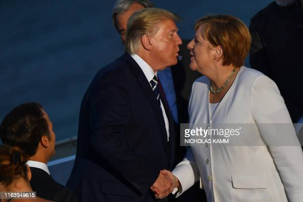 US President Donald Trump shakes hands as he kisses German Chancellor Angela Merkel before posing for a family picture with G7 leaders and guests...