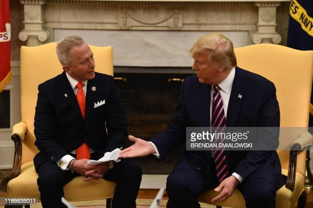 US President Donald Trump shakes hands as he meets with Rep Jeff Van Drew in the Oval Office at the White House on December 19 2019 in WashingtonDC...