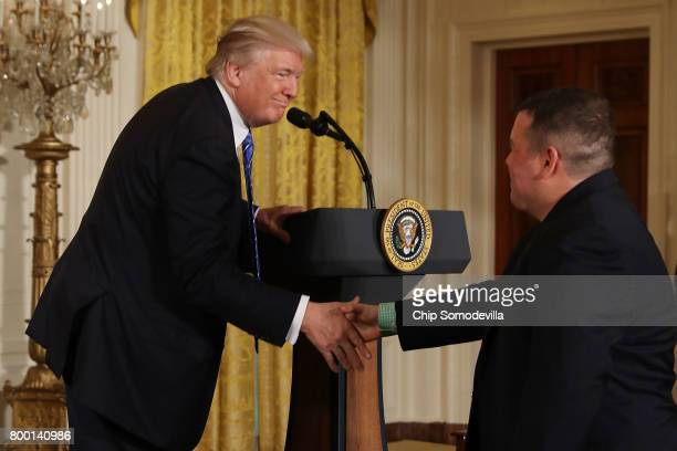 S President Donald Trump shakes hands with Afghanistan war veteran and Purple Heart recipient Michael Verardo during the signing ceremony for the...