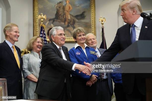 S President Donald Trump shakes hands with Apollo 17 astronaut Jack Schmitt before signing 'Space Policy Directive 1' during a ceremony with Sen Bill...
